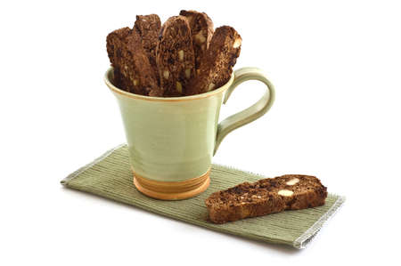 Fresh baked chocolate almond biscotti in green mug on white background