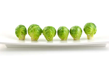 Row of brussel sprouts on long white plate isolated on white background