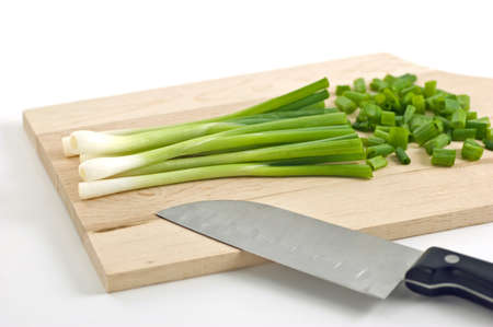 Fresh scallions being chopped on cutting board on white background
