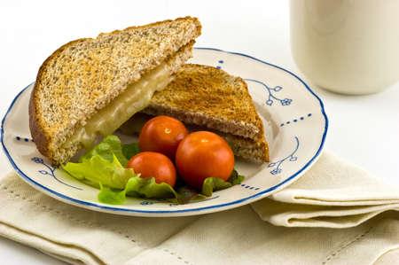 チェリー トマトと全粒小麦のトーストにホワイトチェダー チーズ サンドイッチを焼き