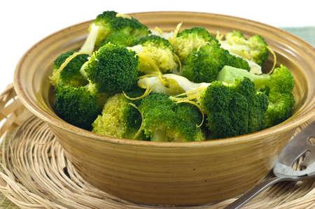 broccoli: Gestoomde broccoli met citroenschil en Parmigiano Reggiano kaas in rustieke gele kom Stockfoto