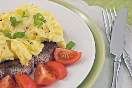 Scrambled eggs on toast with cherry tomatoes on toast Stock Photo