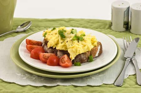 huevos revueltos: Huevos revueltos con tostadas con tomates cherry sobre una tostada