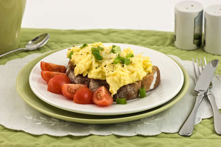 scrambled eggs: Scrambled eggs on toast with cherry tomatoes on toast Stock Photo