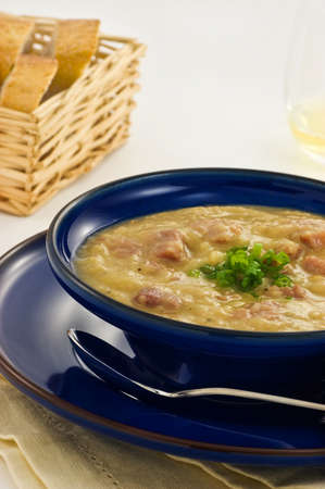 Ham and lentil soup in blue bowl, vertical format