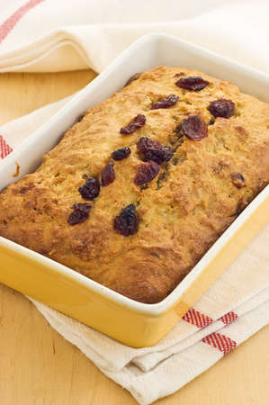 Fresh baked banana bread with dried cranberries in green yellow ovenware dish Stock Photo
