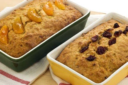 Fresh baked banana bread with dried apricots and dried cranberries in green and yellow ovenware dishes Stock Photo