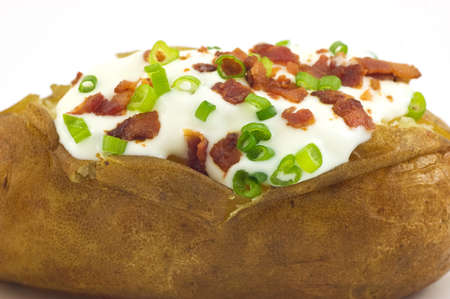 Baked russet potato with sour cream, bacon bits and green onion closeup Imagens