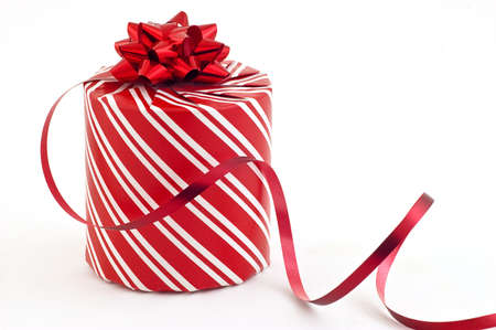 Christmas present in striped red and white paper with ribbon, copy space