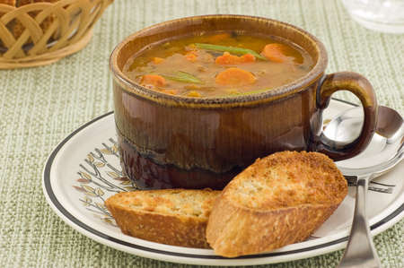 Hearty vegetable soup with artisan baguette in horizontal format Stock Photo - 11498170