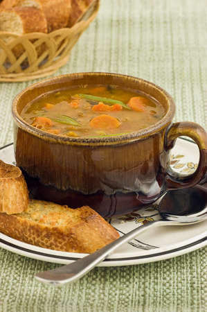 Hearty vegetable soup with artisan baguette in vertical format Stock Photo - 11498168