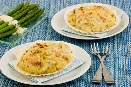 breadcrumbs: Coquille St. Jacques seafood in scallop shells with asparagus Stock Photo