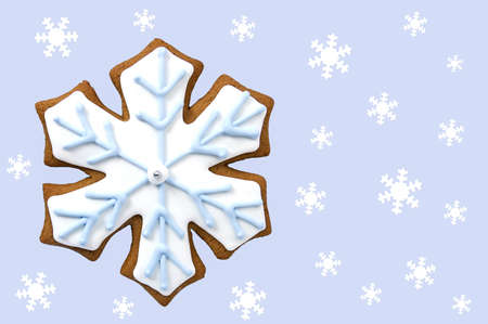 Gingerbread snowflake cookie with tiny white snowflakes on light blue background in horizontal format