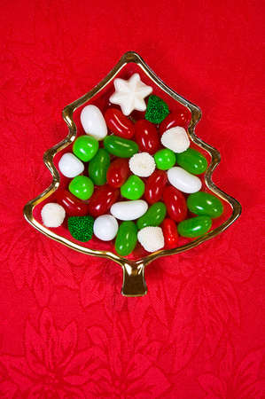 Christmas candy in small glass Christmas tree dish on textured red background, vertical format
