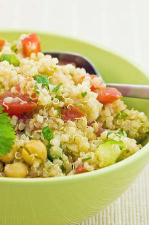 Healthy Quinoa salad in bright green bowl closeup