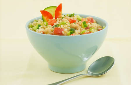 Healthy Quinoa salad in light green bowl on pale yellow background