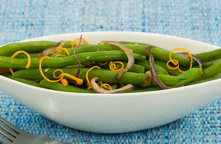 Green beans with caramelized red onion and orange zest in white boat shaped serving dish, on blue textured background
