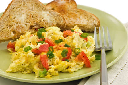 scrambled: Scrambled eggs with red pepper, green onion and cheddar cheese, and warm buttered whole wheat toast Stock Photo
