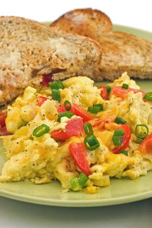 scrambled eggs: Huevos revueltos con pimientos rojos, cebolla y queso cheddar, con agua tibia y pan tostado con mantequilla de trigo integral