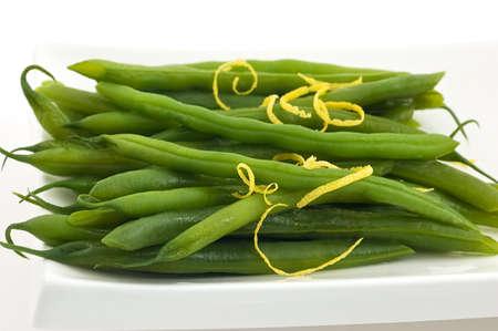 zest: Green beans with lemon zest on white dish