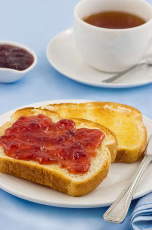 Fresh buttered toast with strawberry jam and tea on blue background