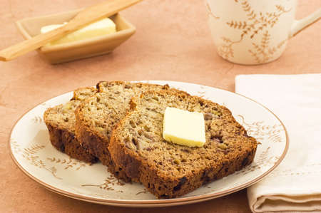 pat: Freshly baked banana bread slices with butter and mug of tea in horizontal format