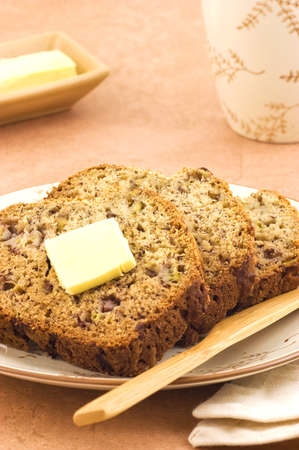 banana slice: Freshly baked banana bread slices with butter and mug of tea in vertical format Stock Photo