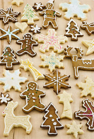 Homemade decorated gingerbread and sugar cookies on wooden board, vertical format photo