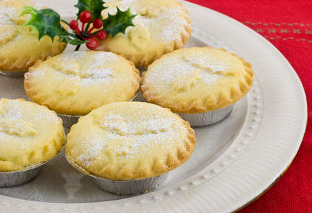 Fresh baked mince tarts with sprig of holly on cream colored plate