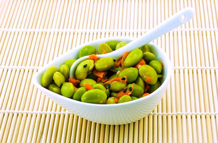 Edamame appetizer in small white dish on bamboo mat Stock Photo