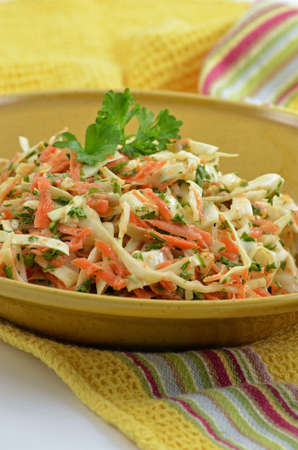 Creamy coleslaw with sweet cabbage, shredded carrots, chopped parsley and shallots in creamy tangy dressing