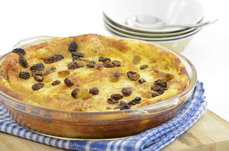 Fresh baked bread pudding with raisins on blue check cloth
