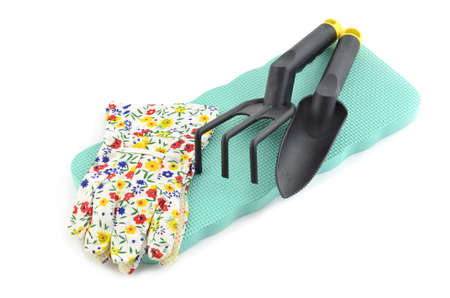 Kneeling pad, gloves and hand gardening tools on white background in horizontal format