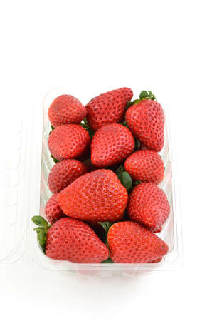 Fresh strawberries in clear plastic container on white background in vertical format with room for copy photo