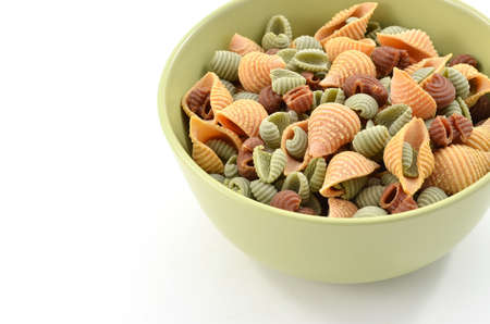 Tri-color pasta shells on white background in horizontal format