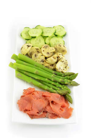 Smoked salmon lox with asparagus, marinated mushrooms and cucumber on white background in vertical format photo