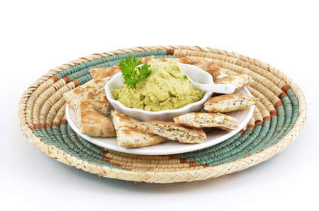 Fresh homemade hummus with pita bread triangles on decorative woven tray with white background in horizontal format