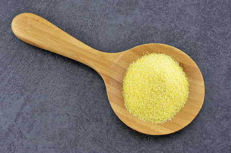 Cornmeal in wooden spoon on slate background Stock Photo