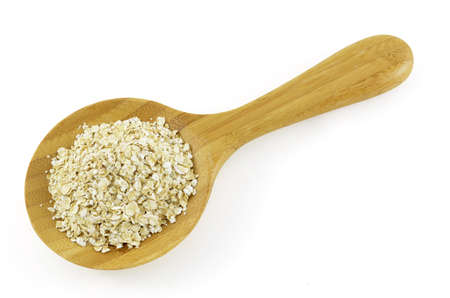 Crushed oats in wooden spoon on white background