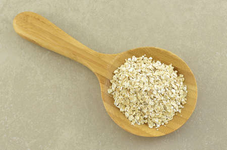 Crushed oats in wooden spoon on sandstone background