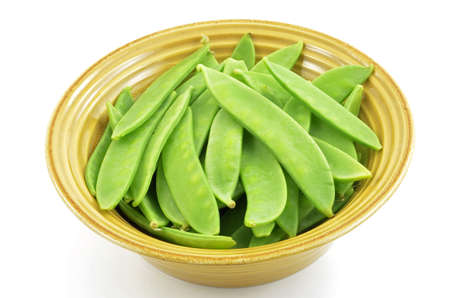 Fresh raw snow peas in golden yellow bowl isolated on white background Stock Photo