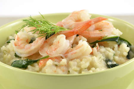 Fresh and creamy Shrimp and Spinach Risotto in green bowl closeup, horizontal format