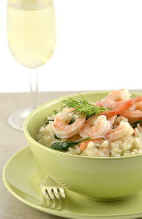 Fresh and creamy Shrimp and Spinach Risotto in green bowl closeup with glass of white wine, vertical format photo