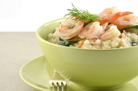 Fresh and creamy Shrimp and Spinach Risotto in green bowl closeup, in horizontal format