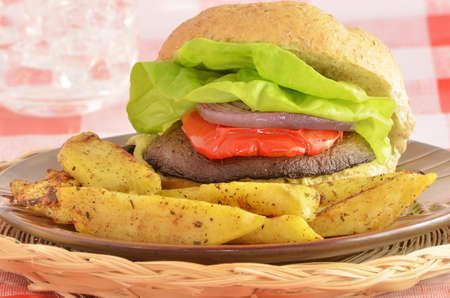 Fresh grilled organic portabella mushroom burger on whole wheat bun with red pepper, red onion, lettuce and spicy wedge sweet potato fries Stock Photo - 12776422