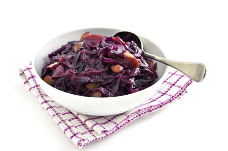 Warm and spicy red cabbage with apple in white dish on white background