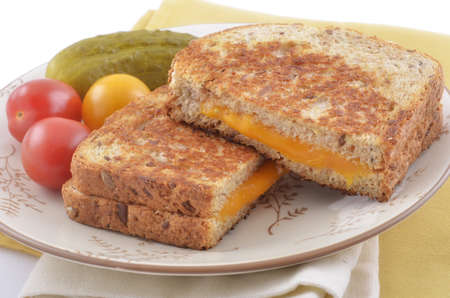 Grilled cheese sandwich on hearty whole grain bread with cherry tomatoes and dill pickle