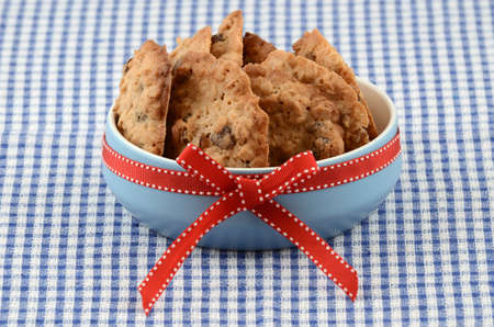 Fresh baked oatmeal and raisin cookies in blue bowl with red ribbon on checked cloth background photo