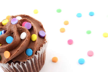 Mini chocolate cupcake with colorful sprinkles on white background Stock Photo