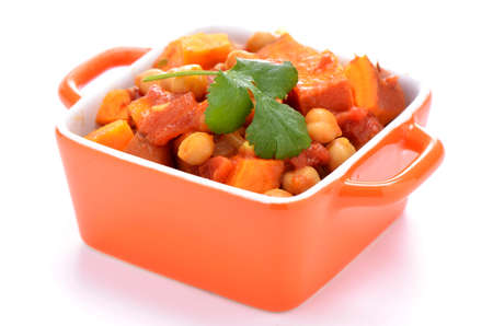 Hearty healthy chickpea and sweet potato curry in small square orange casserole dish on white